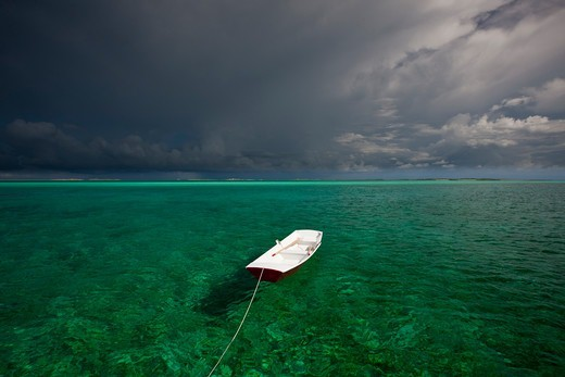 Stock Photo: 4115-4734 Tethered tender floating on clear waters under stormy skies. Exumas, Bahamas, Caribbean. June 2009.