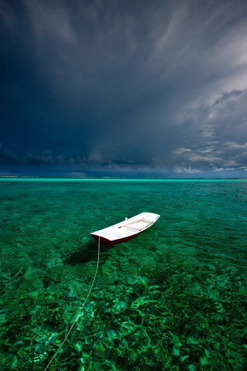 Stock Photo: 4115-4735 Tethered tender floating on clear waters under stormy skies. Exumas, Bahamas, Caribbean. June 2009.