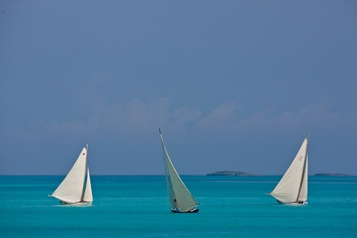 Stock Photo: 4115-4767 Three boats sailing on turquoise seas during the Bahamian Sloop regatta, Georgetown, Exumas, Bahamas. April 2009.