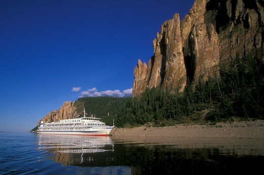 Cruise ship anchored in River Lena off Kembrian stony poles and towers, LenskieStolby nature reserve, Yakutia-Sakha, East Siberia, Russia, August 2005 : Stock Photo