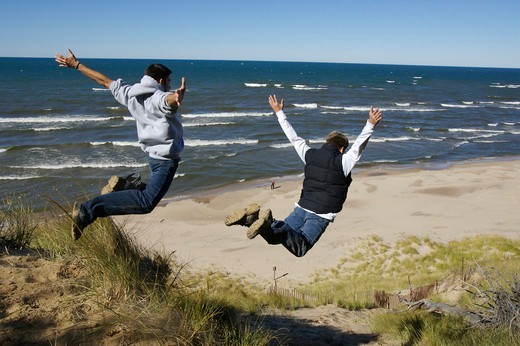 Stock Photo: 4115-5771 Two boys leaping off sand dunes beside Lake Michigan, Holland, Michigan, USA, model released, October 2004