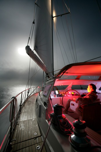 Stock Photo: 4115-607 Man helming Amel 54 ketch 'Hollis' at night, on delivery from Martinique, Caribbean