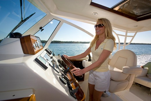 Stock Photo: 4115-637 Woman helming Surf Hunter 33 Jet boat off Marco Island, Florida
