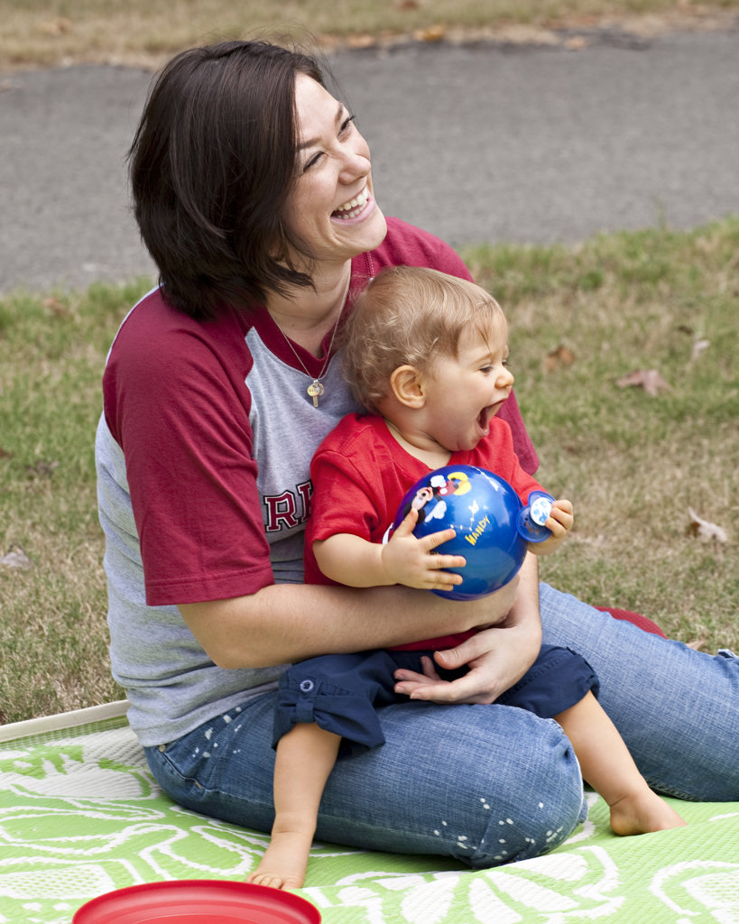 Stock Photo: 4116-295B USA, Arkansas, Mother with baby boy sitting on lawn, laughing