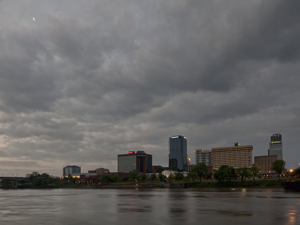Little Rock skyline at dawn, with moon peaking through the clouds : Stock Photo