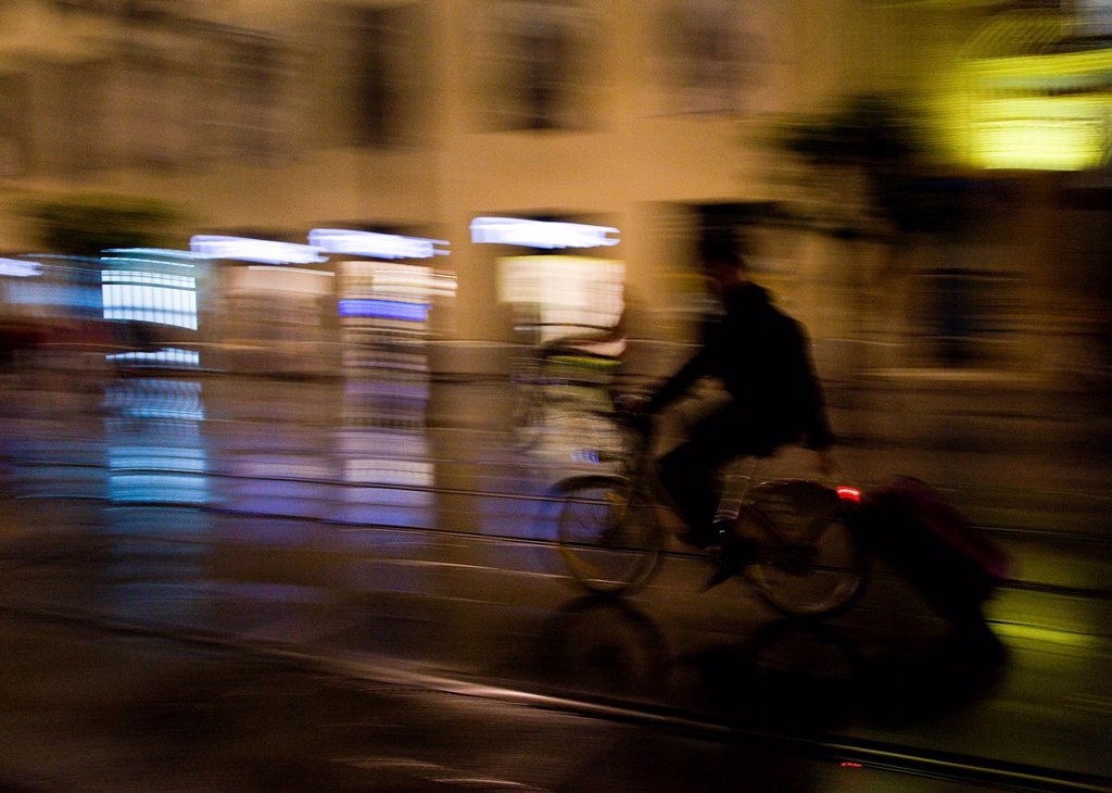 man riding his bicycles and carring a suitcase at night in sevilla, spain : Stock Photo