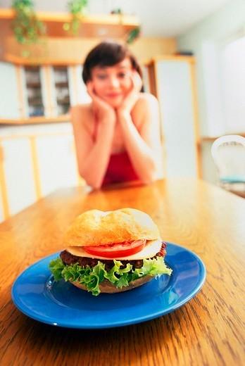 Woman eating hamburger : Stock Photo
