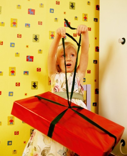 Little girl opening gift : Stock Photo
