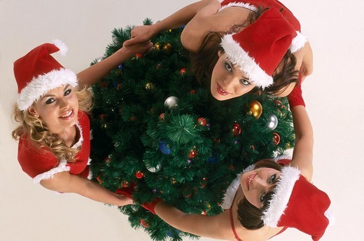 Three girls in christmas disguise at the christmas tree : Stock Photo
