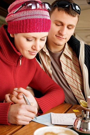 Couple writing postcards : Stock Photo