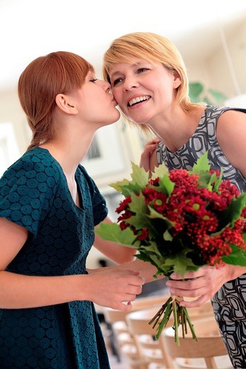 Daughter giving flowers to mother : Stock Photo