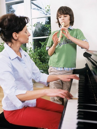 Mother and son playing on instruments : Stock Photo