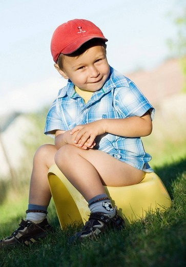 Child boy sitting on a chamber pot. : Stock Photo