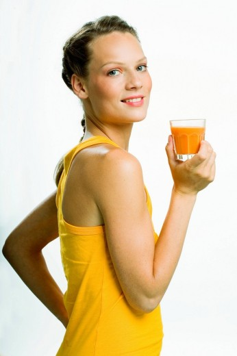 Portrait of a young woman drinking a carrot juice : Stock Photo