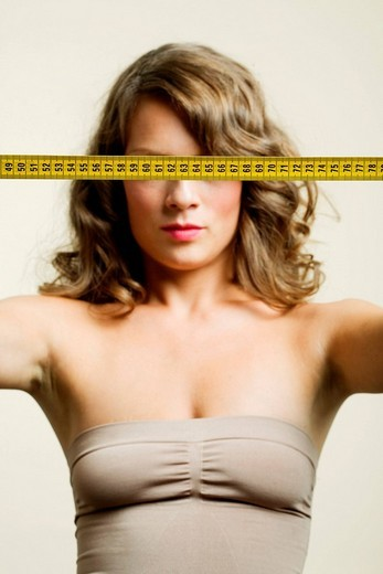 Stock Photo: 4123-27360 Portrait of a young woman with tape_measure