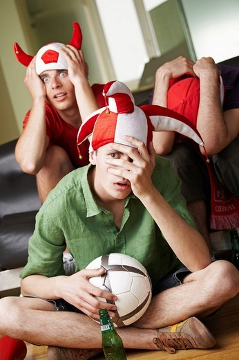 Stock Photo: 4123-27613 Disappointed football fans watching a match in front of tv set.