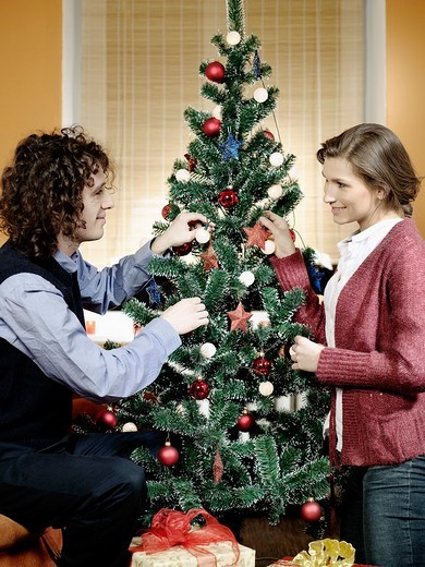 Portrait of a couple decorating a Christmas tree. : Stock Photo