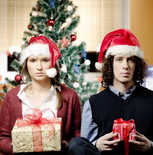 Stock Photo: 4123-28537 Portrait of a couple sitting in living room and sharing gifts.