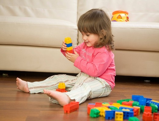 Little girl playing on the floor. : Stock Photo