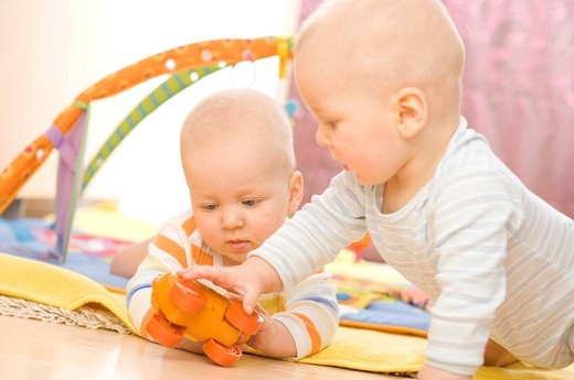 Stock Photo: 4123-30139 Baby twins playing on the floor