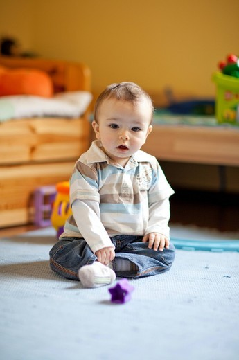 Stock Photo: 4123-30613 Little boy playing on the carpet.