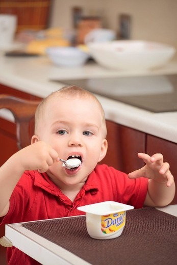 Stock Photo: 4123-31530 Boy eating fromage in the kitchen