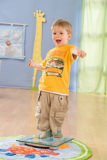 Child standing on a scale : Stock Photo