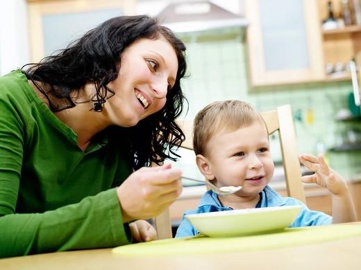 Mother nanny feeding a son. : Stock Photo