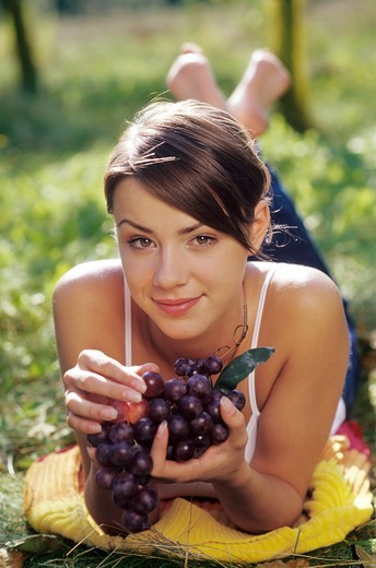 Woman eating grapes in the garden : Stock Photo