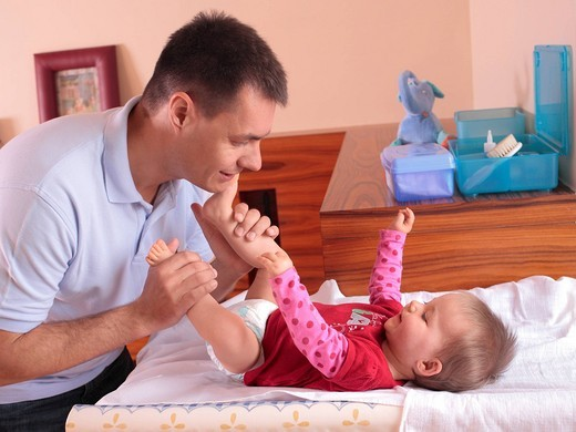 Father changing baby´s diaper : Stock Photo