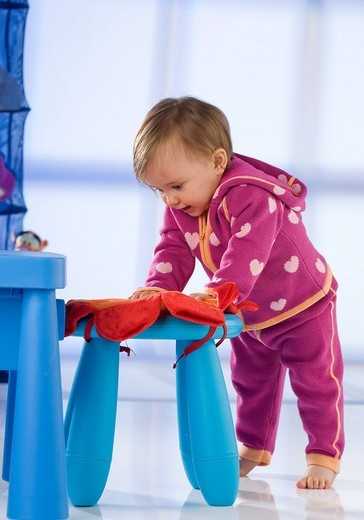 Baby girl while learning how to walk : Stock Photo