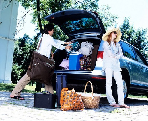 Couple loading their car with luggage. : Stock Photo