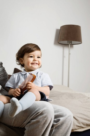 Baby sitting on parent´s knees : Stock Photo