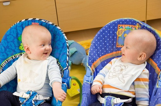 Baby twins gurgling while lying in the cradles : Stock Photo