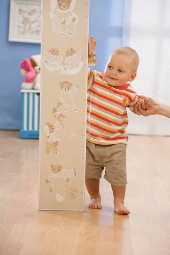 Child standing with a grow chart. : Stock Photo