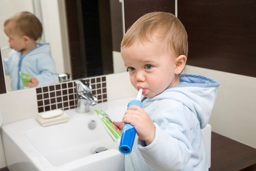 Boy cleaning teeth in the bathroom : Stock Photo