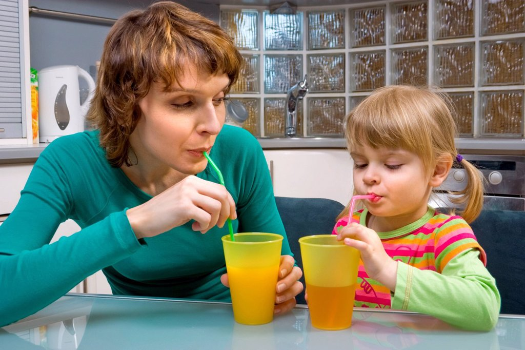 Stock Photo: 4123-38047 Mother and her daughter drinking juice with sippers.
