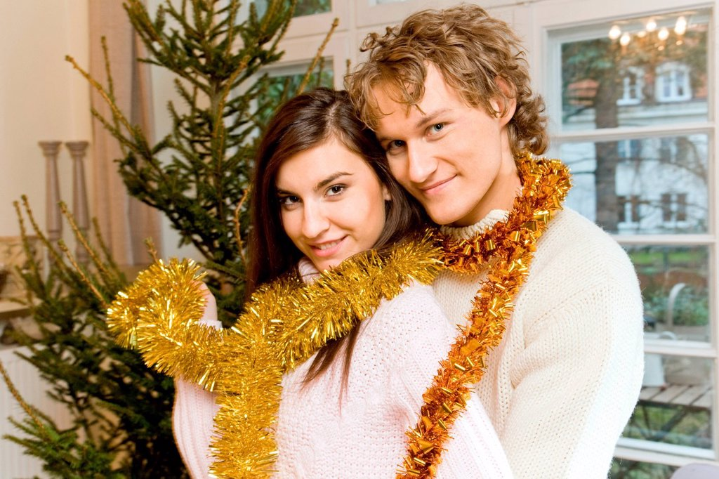 Stock Photo: 4123-38359 Pair decorating Christmas tree.