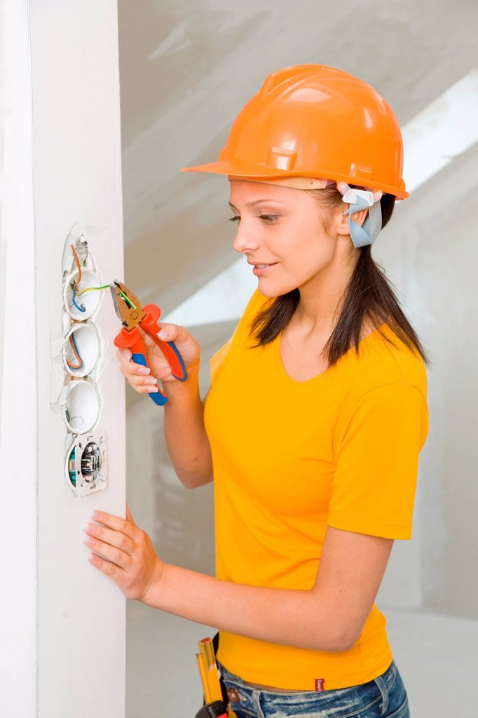Stock Photo: 4123-38956 Young woman using pliers.