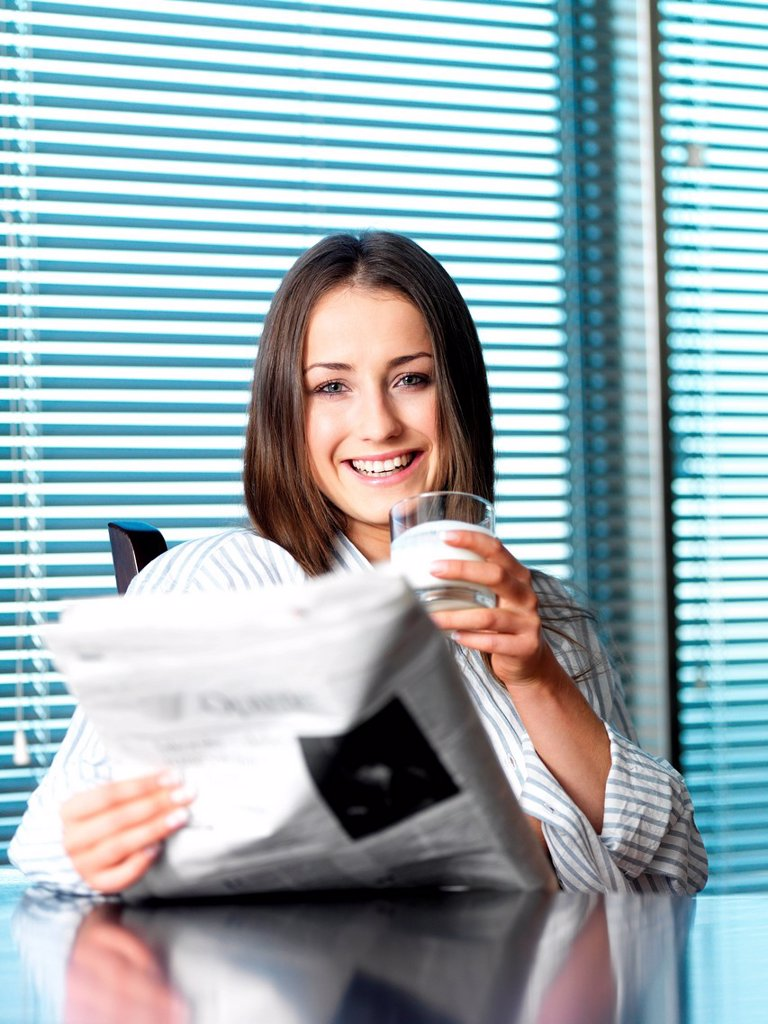 Young woman reading newspaper and drinking milk while sitting in the kitchen : Stock Photo
