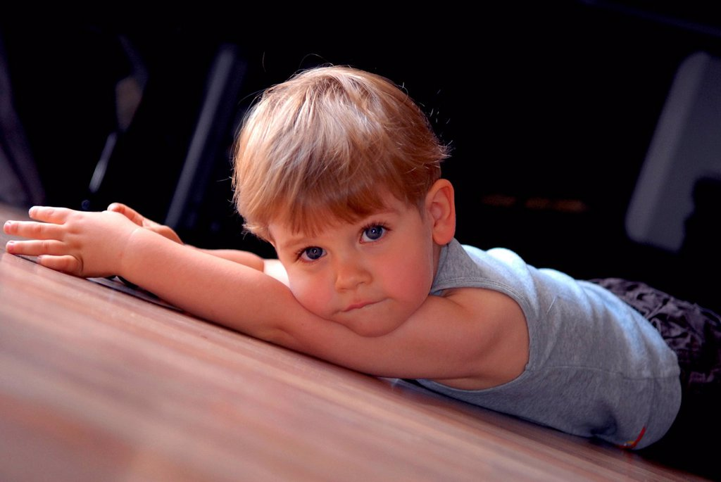 Stock Photo: 4123-39481 Little boy lying on the floor.