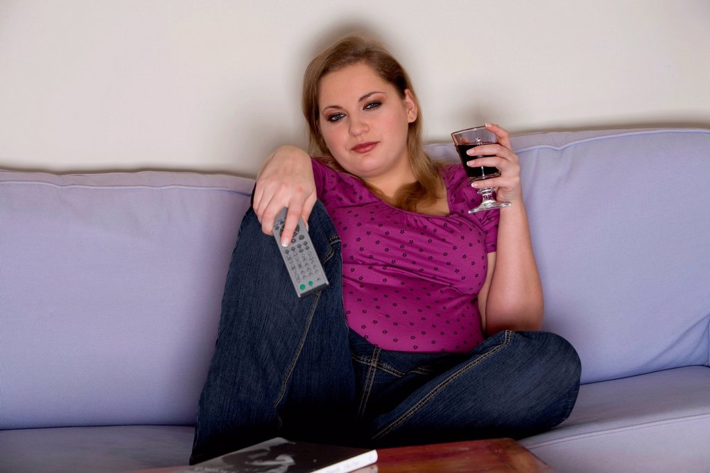 Plump girl watching television : Stock Photo