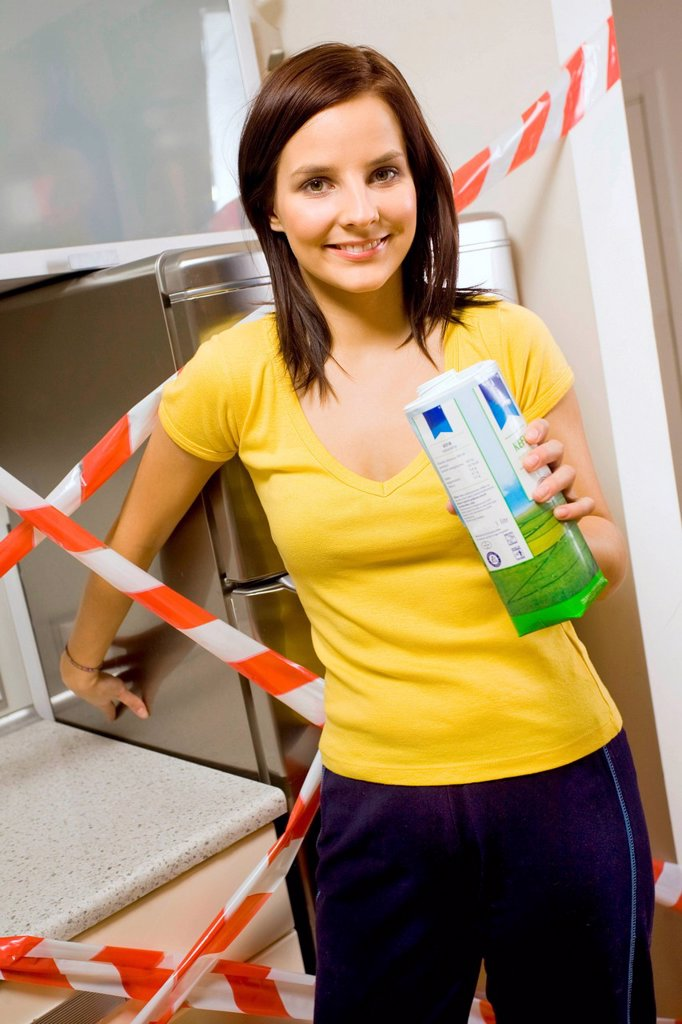 Young woman trying to open the fridge. : Stock Photo