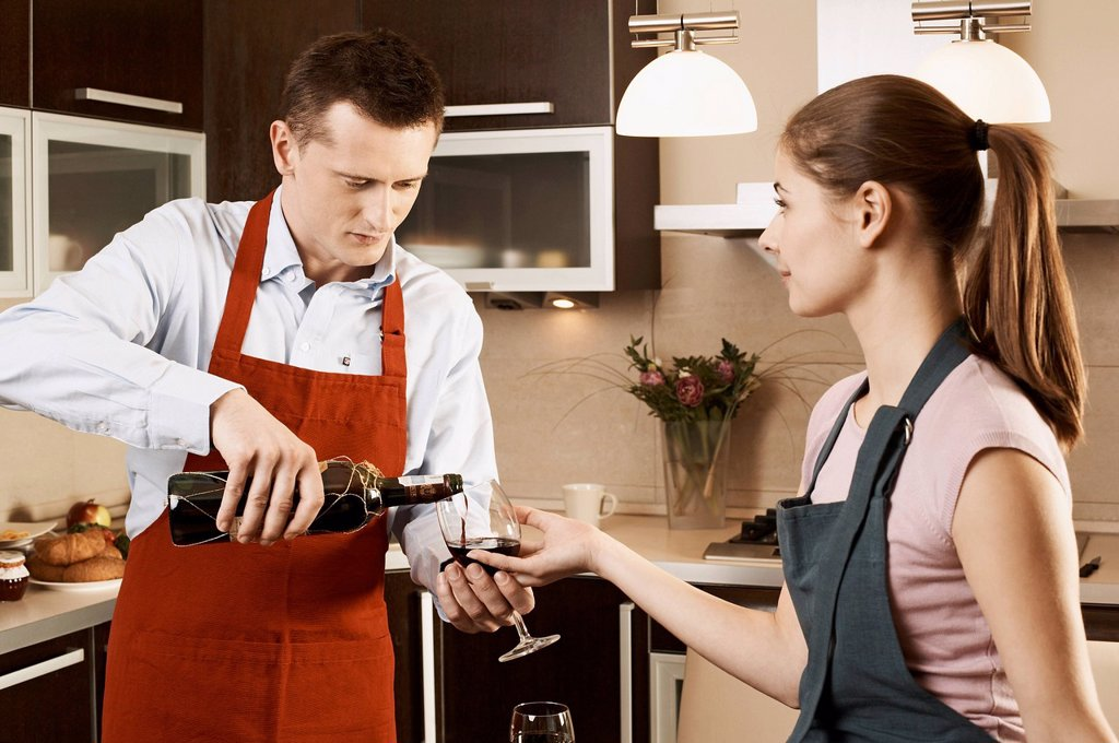 Young couple drinking wine while preparing meal : Stock Photo