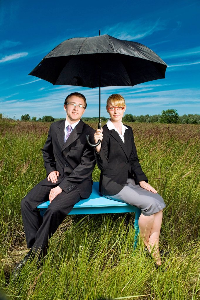 Stock Photo: 4123-42426 Young people on a meadow with umbrella.