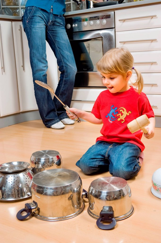 Stock Photo: 4123-42679 Girl drumming on pots with spatula.