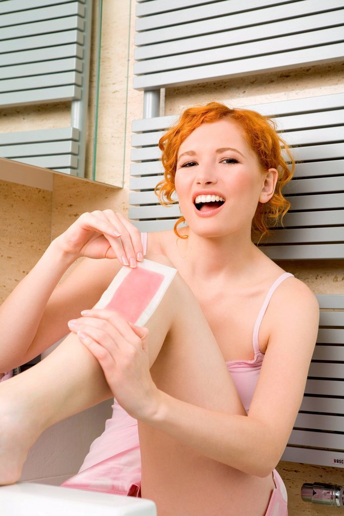 Stock Photo: 4123-42897 Young woman depilating legs.