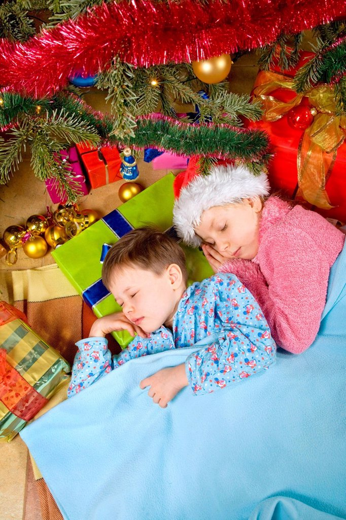 Children sleeping under the Christmas tree. : Stock Photo
