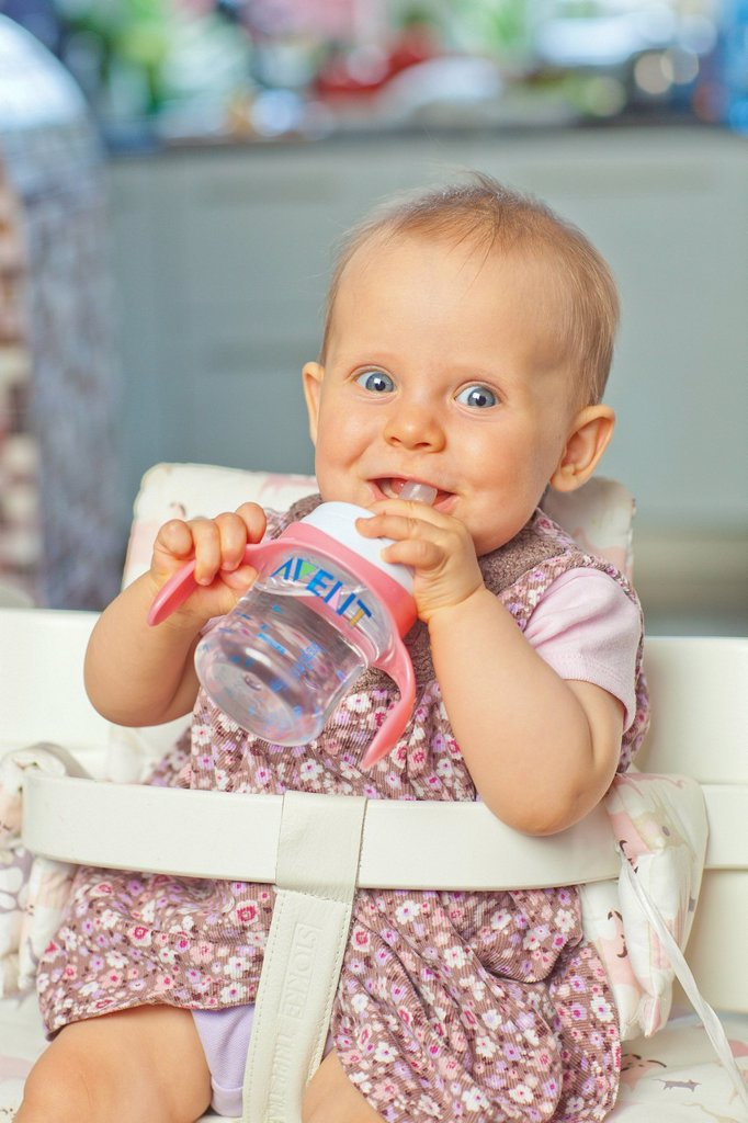 Cute little girl drinking water from cup. : Stock Photo