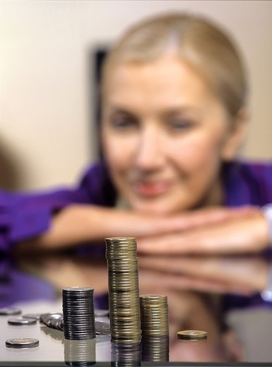 Pile of coins against a smiled woman. : Stock Photo